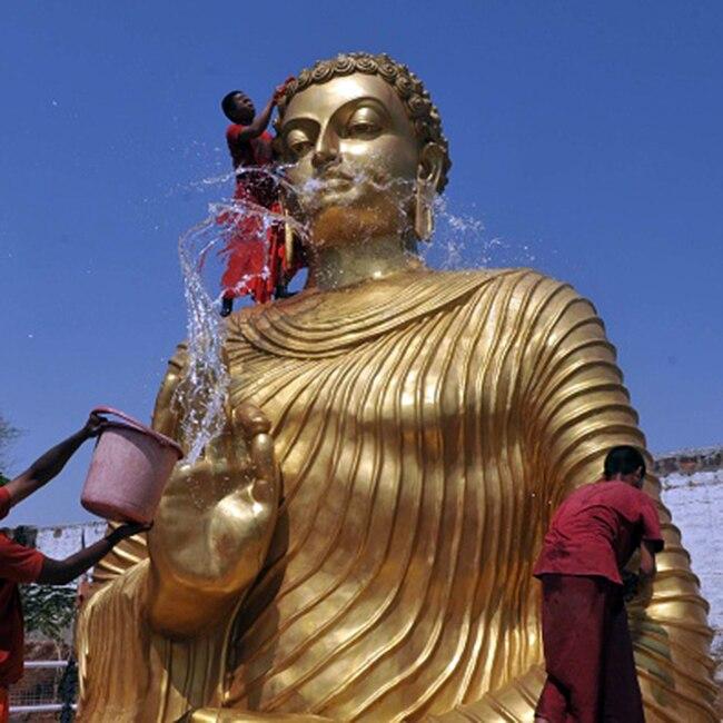 Buddhist monks cleaning Buddha idol in Bhopal
