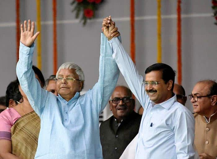 Lalu Prasad Yadav greets crowd along with Arvind Kejriwal during the swearing-in ceremony