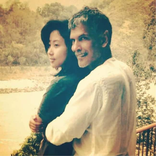 Milind Soman posing with his girlfriend