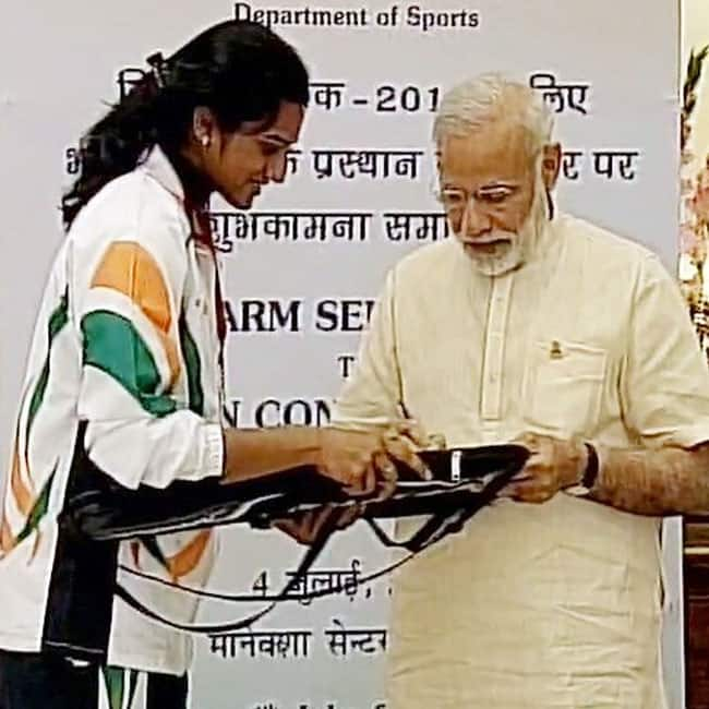Narendra Modi signing an autograph as he meets athlete representing India at Rio Olympic 2016