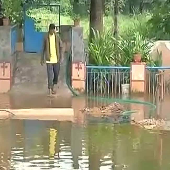 People walking through the flooded roads during heavy rain in Hyderabad