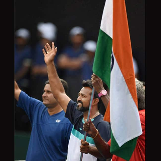 Tennis player Leander Paes hosting the Indian national flag post win in Pune   s Davis Cup
