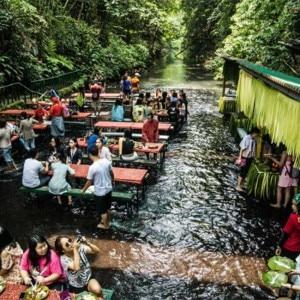 Tourists Enjoying At Labassin Waterfall Restaurant In