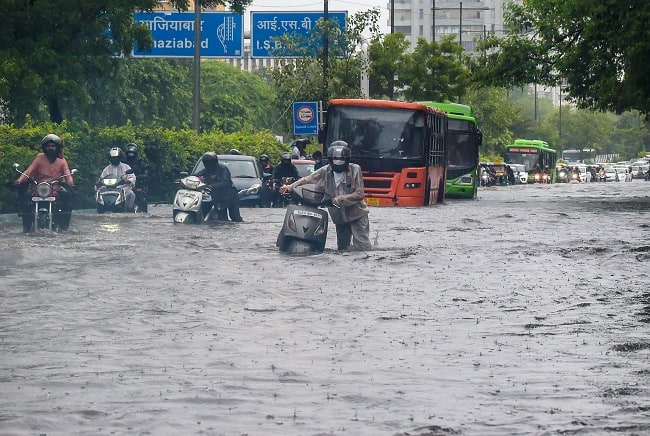 Commuters push their scooters through a waterlogged road near ITO