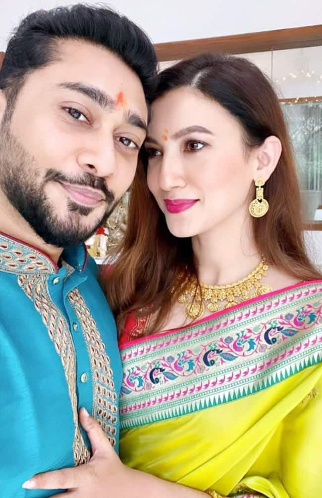 Gauahar Khan looks lovely in a neon yellow saree which she teamed with a pink blouse  husband Zaid looks dapper in a blue kurta