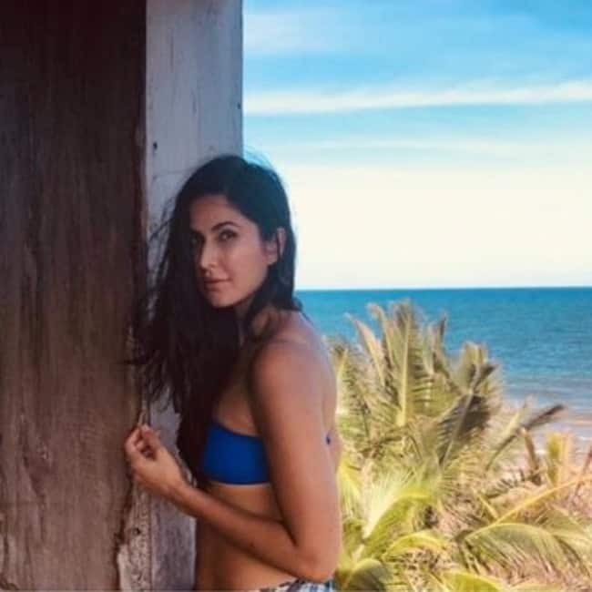 Katrina poses in blue swimwear in a beach