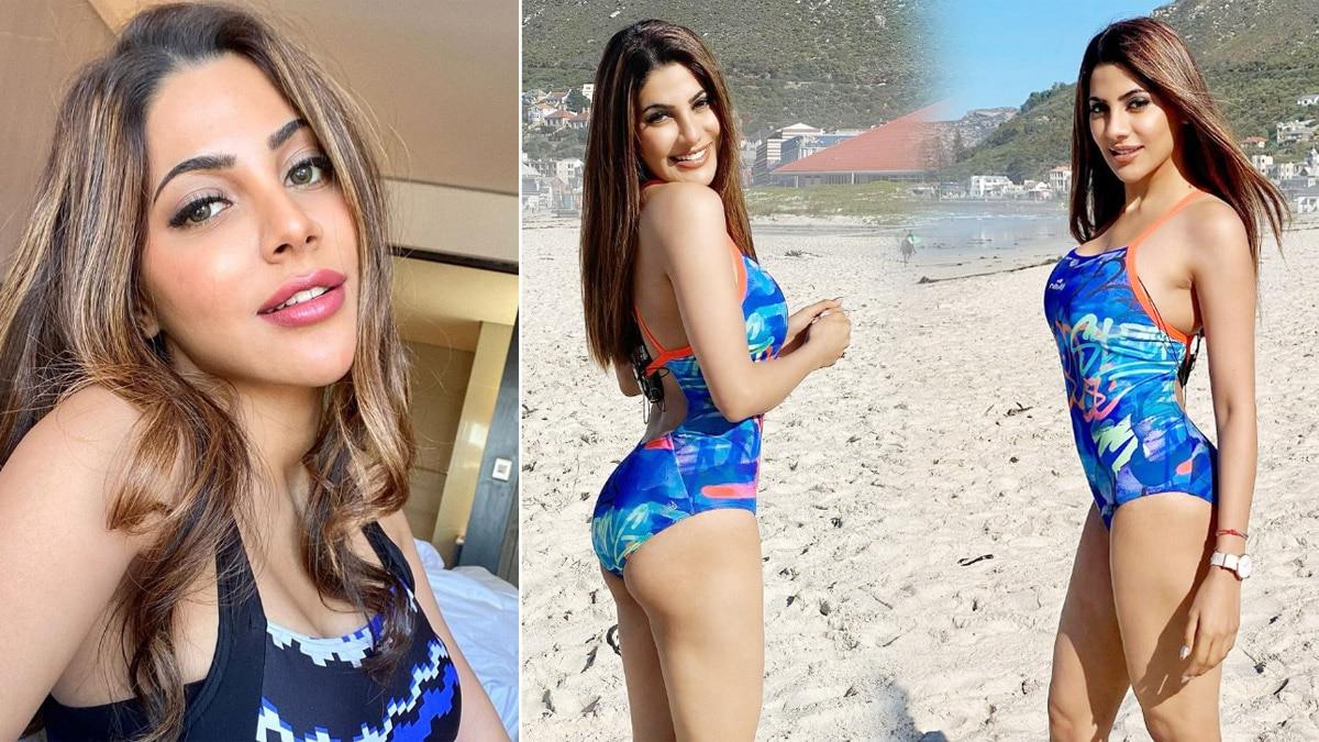 Nikki Tamboli Poses in A Blue Swimwear on A Beach