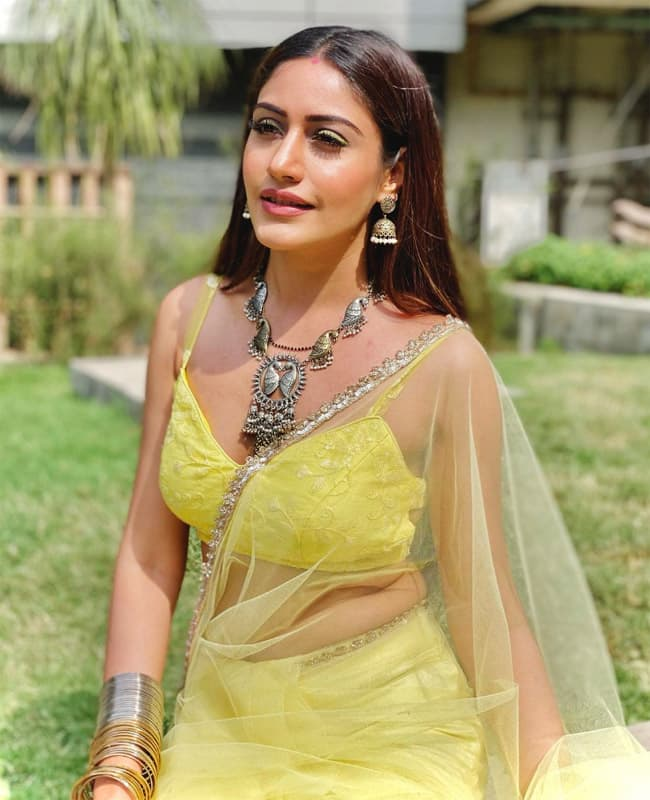 Surbhi Chandna shows off her curves in a yellow saree