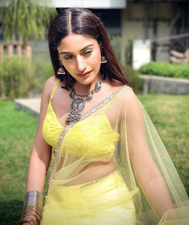 Surbhi Chandna wears a yellow backless blouse with a net saree