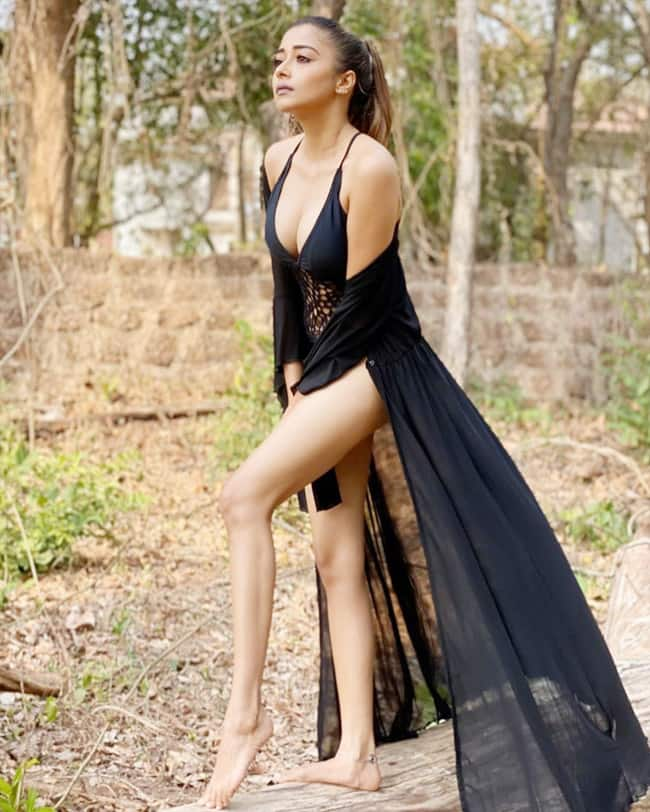 Tina Datta poses amid woods wearing a black lace monokini